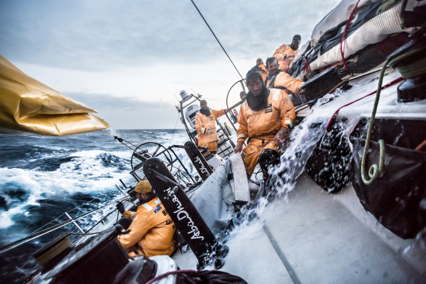 April 1, 2015. Leg 5 to Itajai onboard Abu Dhabi Ocean Racing. Day 15.  Louis Sinclair wrestles a sailbag in the cockpit in the midst of a very wet sail peel in the Brazilian Current of the Atlantic Ocean